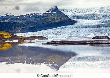 Glacier meltwater form a picturesque lake. The sunset over...