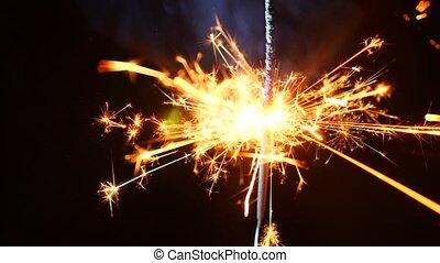 Firework sparkler burning in macro shot on a black...