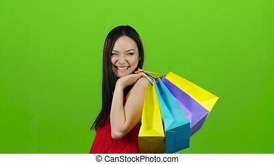 Girl of Asian appearance goes shopping, with paper. Green...