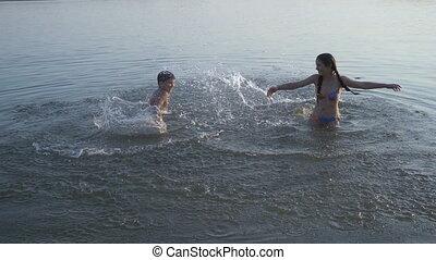 two kids splashing water in river at sunset - two kids...
