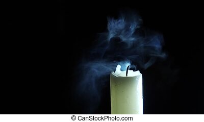 closeup of candle on black. Dying out the flame of a white...