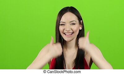 Girl s having fun and showing a thumbs up. Green screen. Slow motion