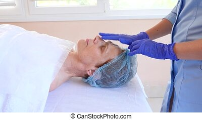 Spa therapy for elderly woman receiving facial mask. 4k....