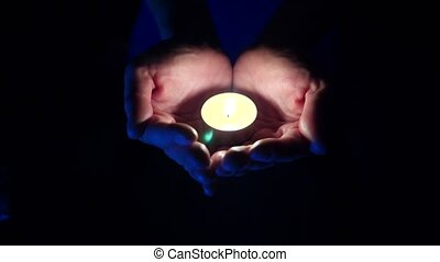 Closeup of an aromatic little candle in the palms of a man...