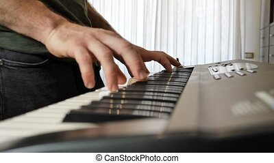 Man playing electric piano or electronic keyboard - Side...