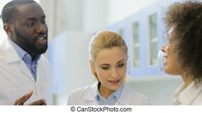 Group Of Scientist Discuss Experiment In Lab Making Notes,...