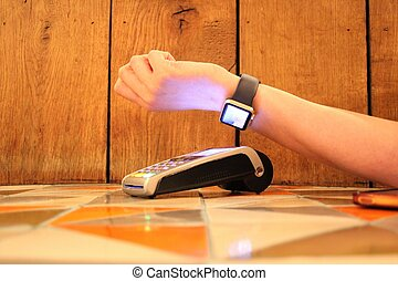 contactless payment smartwatch pdq with hand holding credit...