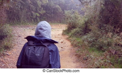 Following to tourist girl with backpack that walking along...