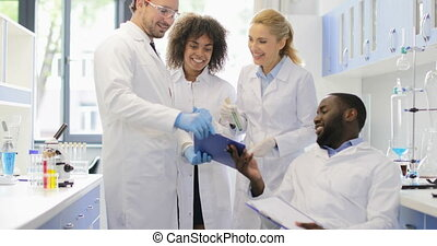 Happy Team Of Scientists Discussing Result Of Experiment...
