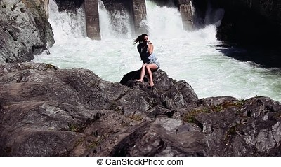 Beautiful girl posing sitting on the rocks. Behind her falls waterfall