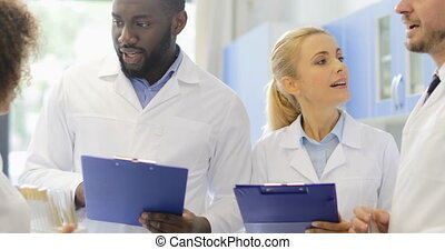 Happy Smiling Scientists Team Talking Holding Documents With...