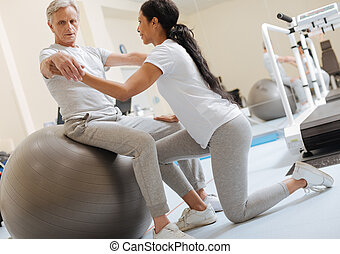 Serious invalid man doing rehabilitation exercises