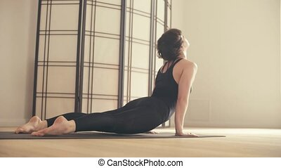 A young woman performing yoga-asanas in the hall. Ardha...
