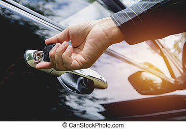 Close-up of man opening a car door. Hand on handle. Businessman is opening a car.