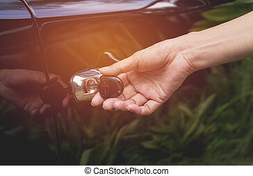 Close-up of woman opening a car door. Hand on handle. Female is opening a car.