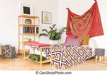 Cozy ethnic bedroom with wooden bookstand and oriental...