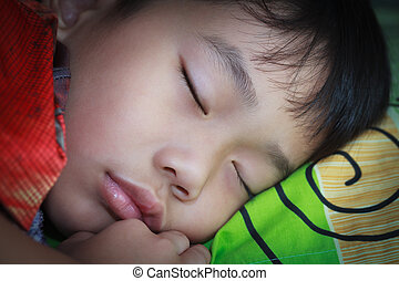 Healthy child. Closeup asian boy sleeping peacefully on bed....