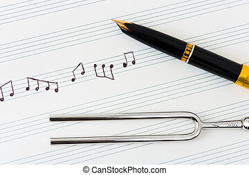 Pitchfork and pen on music sheet - abstract art background