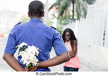 proof of love. - This young man hides a flower in his back...
