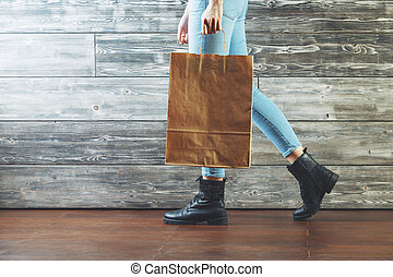 Consumerism concept - Side view of walking female legs with...