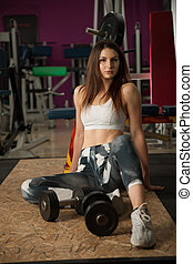 active young woman rests after workout in fitness club gym