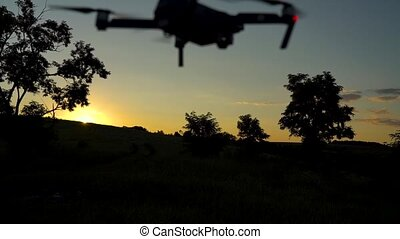 Silhouette of small quadrocopter flying against the sky -...