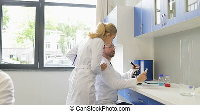 Scientist Woman Coming To Researcher Man Working With...