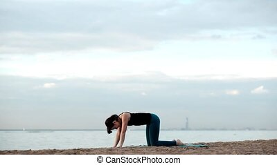 Caucasian thin pretty woman yoga on the beach. Healthy...
