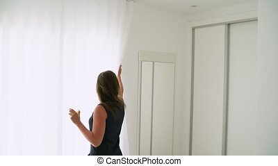 Woman opening her bedroom curtains and drinking orange juice in slow motion