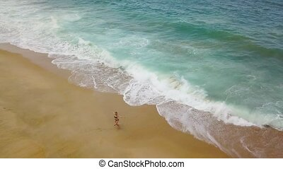 Beach bikini woman carefree is spinning her arms out to the...