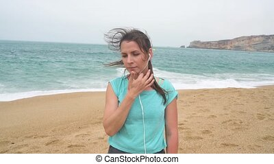 Woman on beach listening to music on headphones from smart phone. Nazare, Portugal