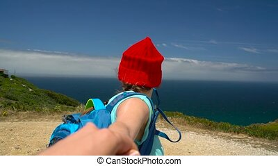 Follow me - happy young woman in a red hat and with a backpack behind her back pulling guy's hand. Hand in hand walking to the ocean coast