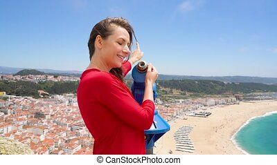 Female tourist using coin paid binoculars on high hill and...