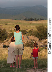Children - A family looks over a meadow and the mountains of...