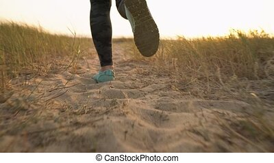 Female legs running along a sandy beach to the ocean. Slow...