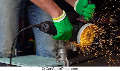 Male worker with angular grinding machine is cutting the...