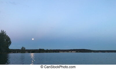 evening landscape with a moon in the sky and Lake