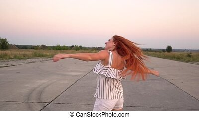 Happy red-haired woman whirls, her hair fluttering in the wind