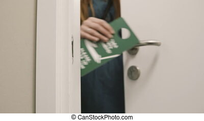 Close-up view of young woman comes out from the room in hotel and puts on knob the door hanger, asking to clean the room