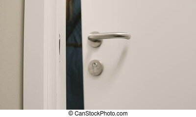 Close-up view of young woman comes out from the room in hotel and puts on knob the door hanger, asking do not disturb.