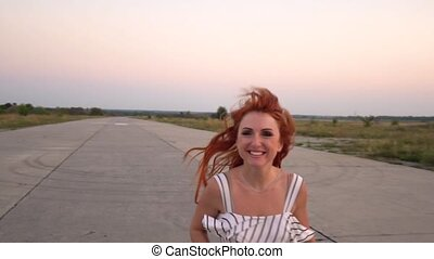 Cheerful red-haired woman runs to the camera with a frightening expression