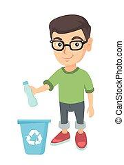 Boy throwing plastic bottle in recycle bin.