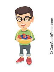 Boy with the basket of strawberry and blueberry.