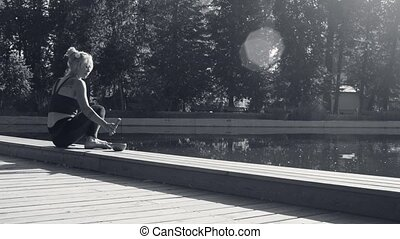 Young woman meditating in the park near the lake at summer...