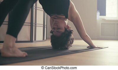 A young woman performing yoga-asanas in the hall. Surya...