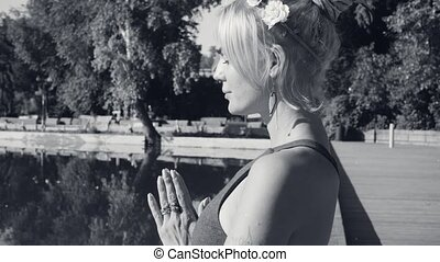 Portrait of young woman meditating near the lake in the park...