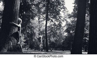 Young woman hugging a big tree in the park