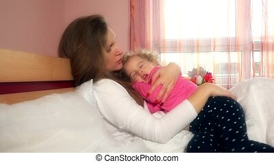 Young mother holding and swinging her toddler child girl on hands in bed