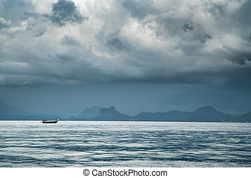 boat on the sea during storm coming with dark cloud.