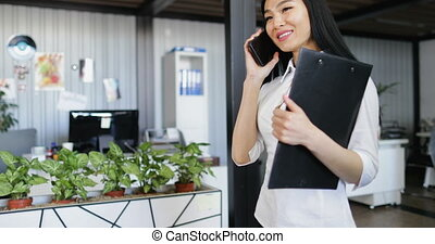 Asian Business Woman Talking On Phone Call Holding Documents...